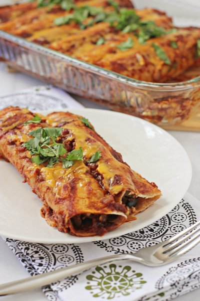 Two Chicken and Vegetable Enchiladas on a plate.