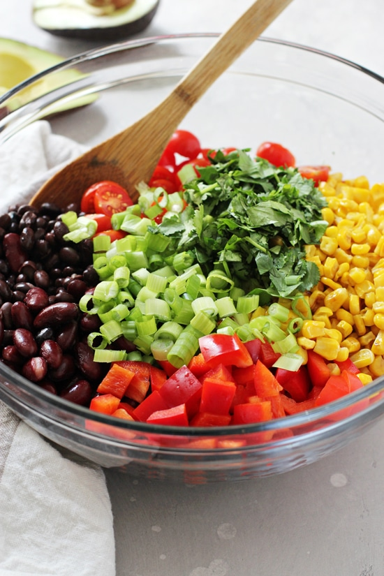 A glass bowl filled with all the components for Southwestern Bean Salad with a wooden spoon in the dish.