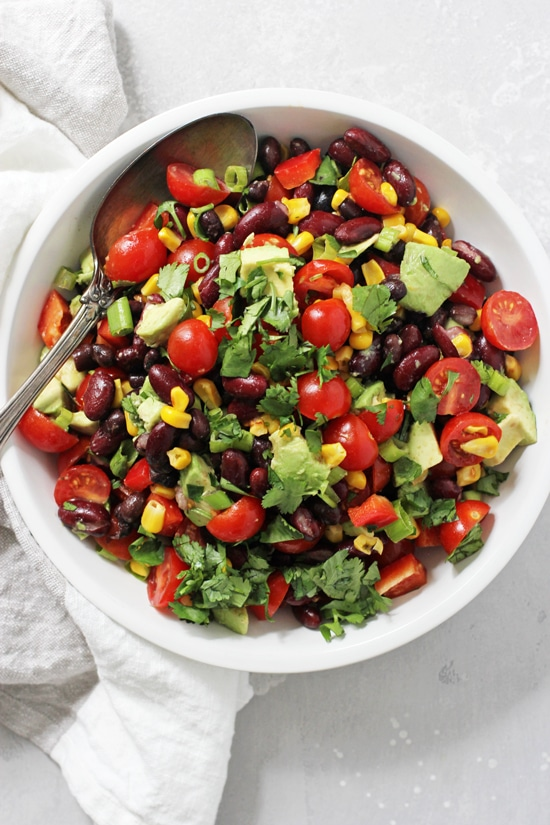 A white bowl filled with Mexican Black Bean Salad with a silver serving spoon in the dish.
