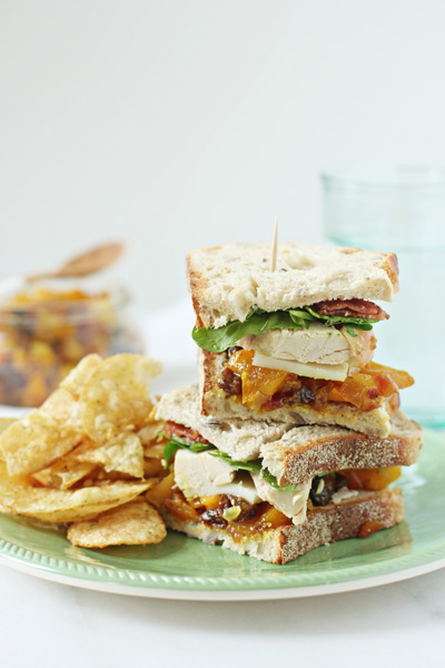 A stacked Chicken and Chutney Sandwich on a plate with chips.