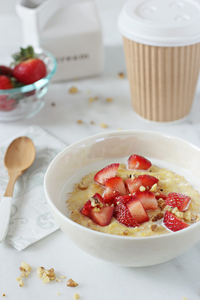 A bowl of Strawberry Polenta with a spoon and coffee to the side.