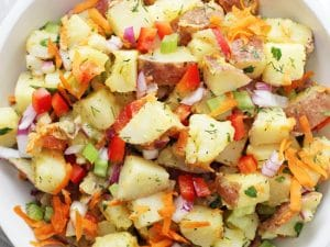 Crunchy, creamy and packed with flavor, this dairy free potato salad is perfect for summer parties and potlucks! With fresh veggies and a dreamy maple mustard dressing, there's no mayo involved! Gluten free & vegan.