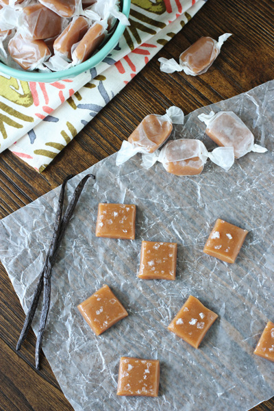 Wrapped and unwrapped Vanilla Bean Caramels scattered on parchment.