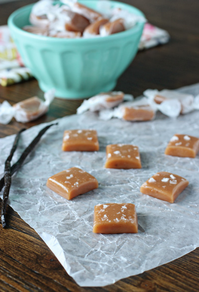 Several unwrapped Vanilla Bean Sea Salt Caramels on parchment paper.
