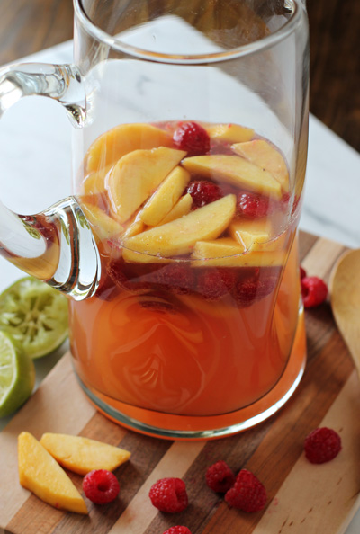 A glass pitcher of Peach and Raspberry Sangria on a wood cutting board.