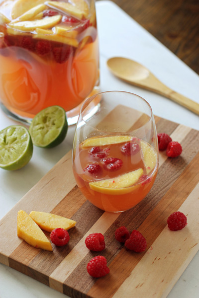 A glass and pitcher of Peach Raspberry Sangria on a wood surface.