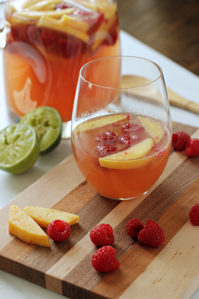 A glass of Raspberry Peach Sangria set on a cutting board.
