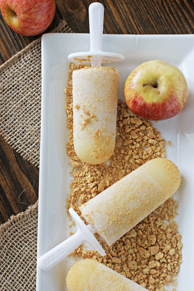 Three Apple Pie Ice Pops on a white tray with graham crackers.