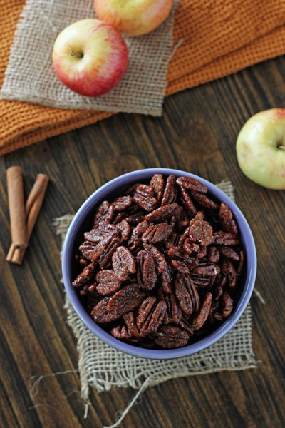 A bowl filled with Apple Spice Pecans with fresh apples to the side.