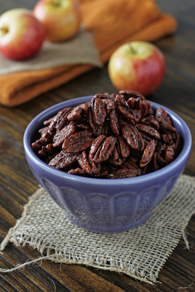 A purple dish filled with Apple Pie Spiced Pecans.