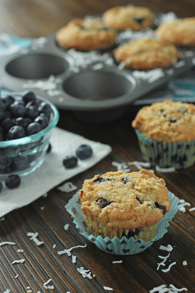 Two Coconut Blueberry Muffins on a wood surface with more to the side.