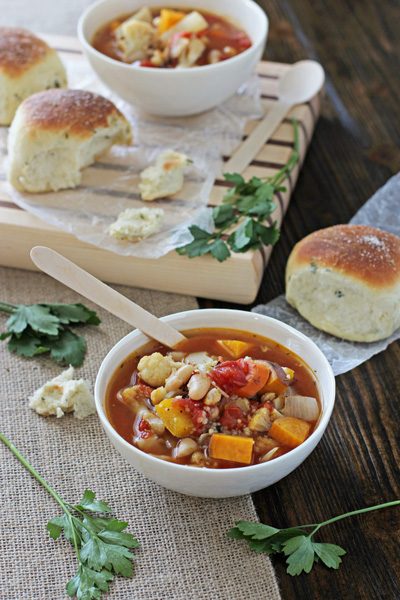 Two bowls of Roasted Veg Soup with rolls to the side.