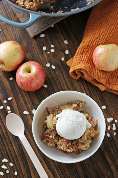 A serving of Cast Iron Apple Crisp in a white bowl with ice cream.