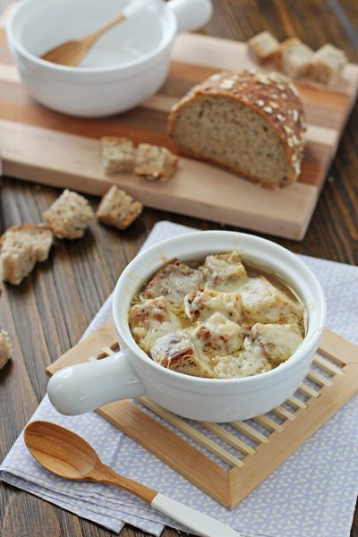 A white bowl filled with Slow Cooker French Onion Soup.