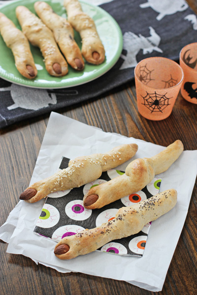 Several Witches' Finger Breadsticks on napkins and a green plate.