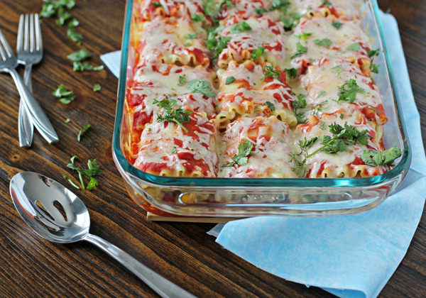 A glass baking dish of Mexican Lasagna Rolls with a serving spoon to the side.