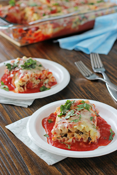 Two white plates with servings of Mexican Lasagna Roll-Ups.