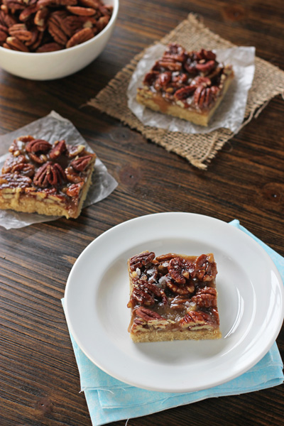 Three Salted Pecan Pie Cookie Bars on a plate and parchment paper.