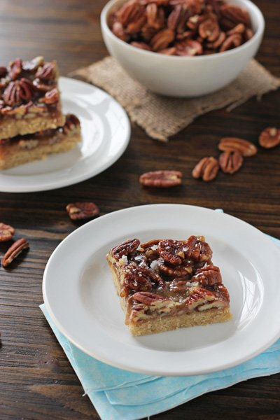 Several Salted Pecan Pie Bars on white plates.