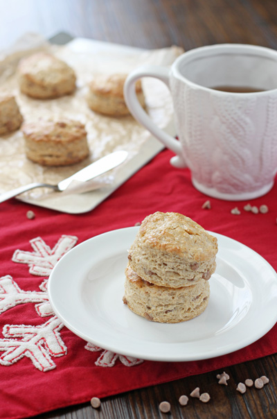 Two Eggnog Biscuits stacked on a plate with more in the background.