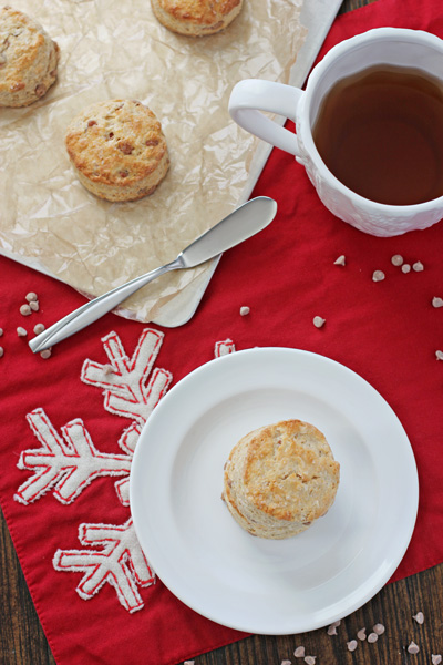 Eggnog Biscuits on a plate and baking sheet with tea to the side.