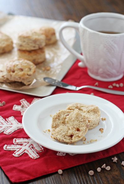 A split open Eggnog Biscuit on a plate with tea to the side.