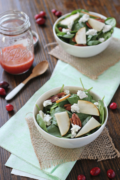 Two spinach salads topped with Fresh Cranberry Vinaigrette.