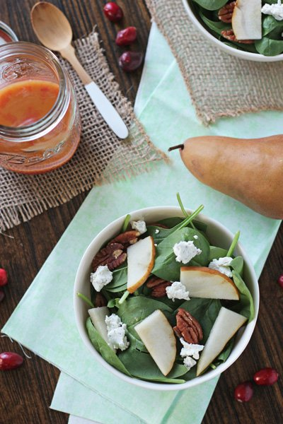 A Winter Spinach Salad in a white bowl with cranberry dressing to the side.