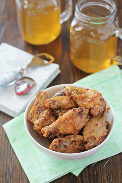 A bowl filled with Honey Chipotle Wings with two beers to the side.
