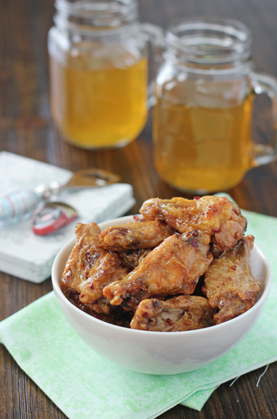 A bowl of Chipotle Chicken Wings with beers in the background.
