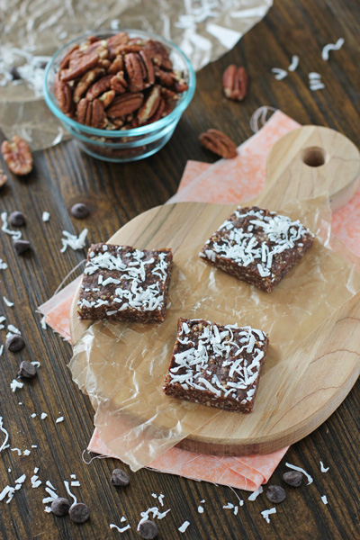 Three No Bake Brownies on a cutting board with pecans to the side.