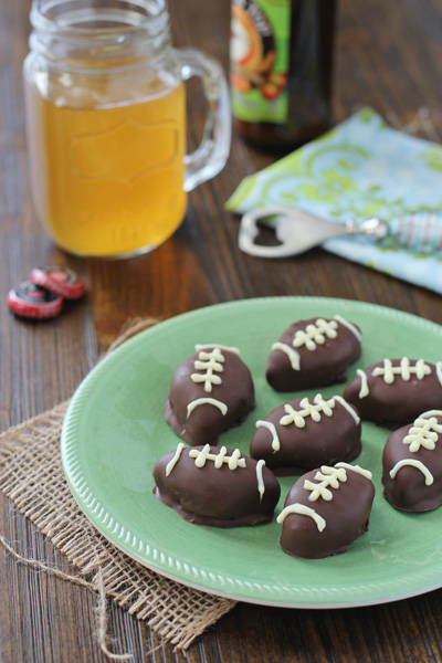 A green plate filled with Oreo Football Truffles.