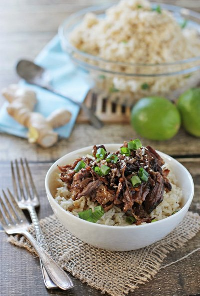 Crockpot Beef Short Ribs over rice in a white bowl with forks to the side.