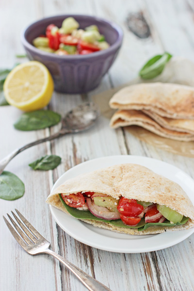 A Mediterranean Pita Pocket on a plate with veggies and pita bread to the side.