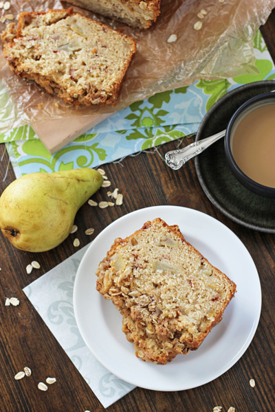 Two slices of Pear Quick Bread on a plate with coffee to the side.