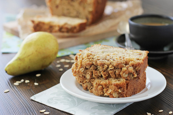 Two slices of Pear Bread with Oat Streusel on a plate with a pear to the side.