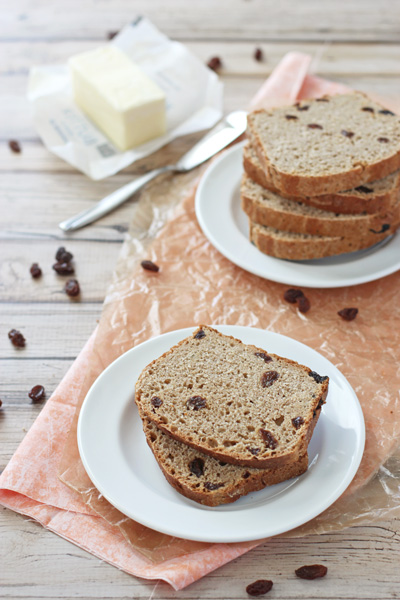 Several slices of Quicker Cinnamon Raisin Bread on white plates.