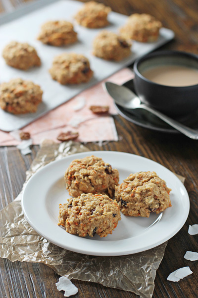 Three Healthy Carrot Cake Cookies on a white plate with coffee to the side.