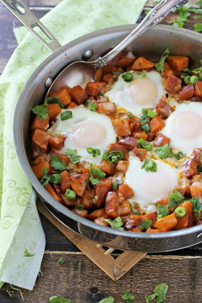 A Sweet Potato Breakfast Skillet on a wooden surface with a spoon in the dish.