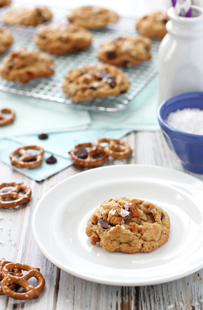 A Chocolate Chip Peanut Butter Pretzel Cookie on a plate with more in the background.
