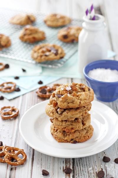 Four Peanut Butter Pretzel Cookies stacked on a white plate.