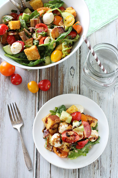 A white plate and serving bowl filled with BLT Panzanella.