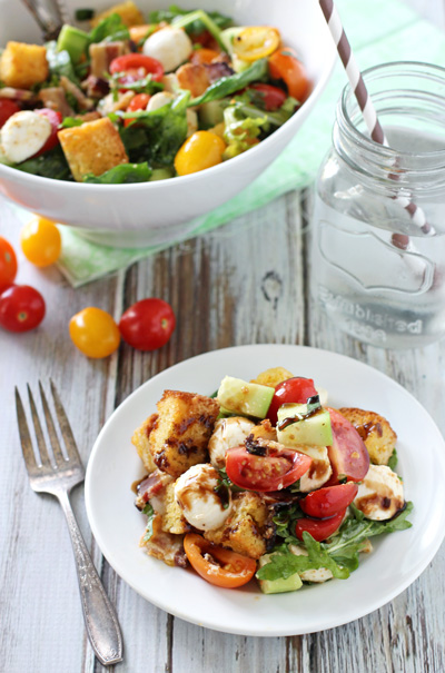 A white dish and serving bowl filled with Cornbread Panzanella.