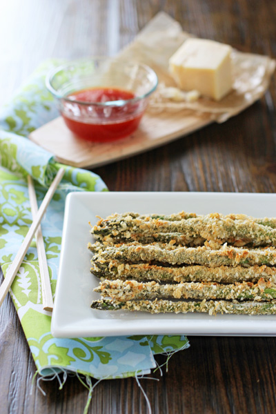 Parmesan Crusted Asparagus on a white serving platter with sauce to the side.