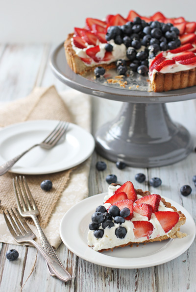 A slice of Berry Mascarpone Tart on a plate with the full tart in the background.