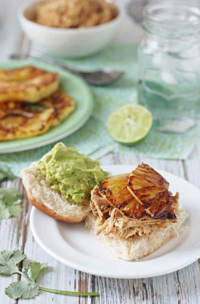 Crockpot Pineapple Chicken piled on a roll with guac and pineapple slices.