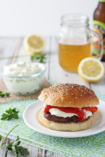 A Mediterranean Burger on a white plate with beer in the background.