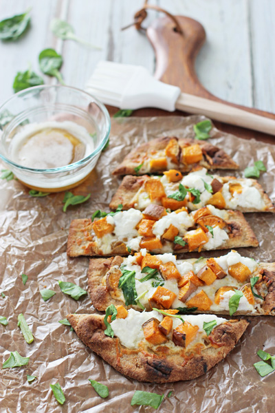 A sliced up Sweet Potato Flatbread on a wooden pizza peel.