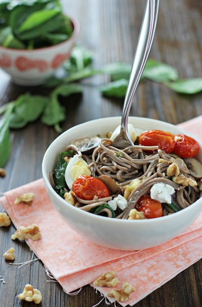 A white bowl filled with Soba Noodles with Tomatoes with a fork in the dish.