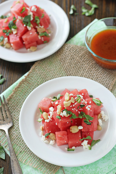 Two white plates filled with Watermelon and Feta Salad with dressing to the side.